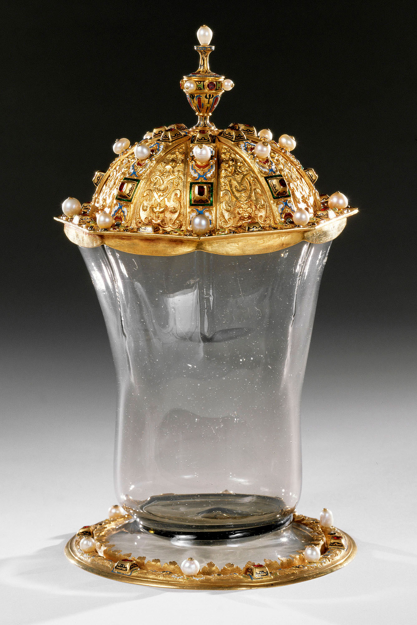 Clear glass vessel with gold trim at base and gold, jewelled lid.