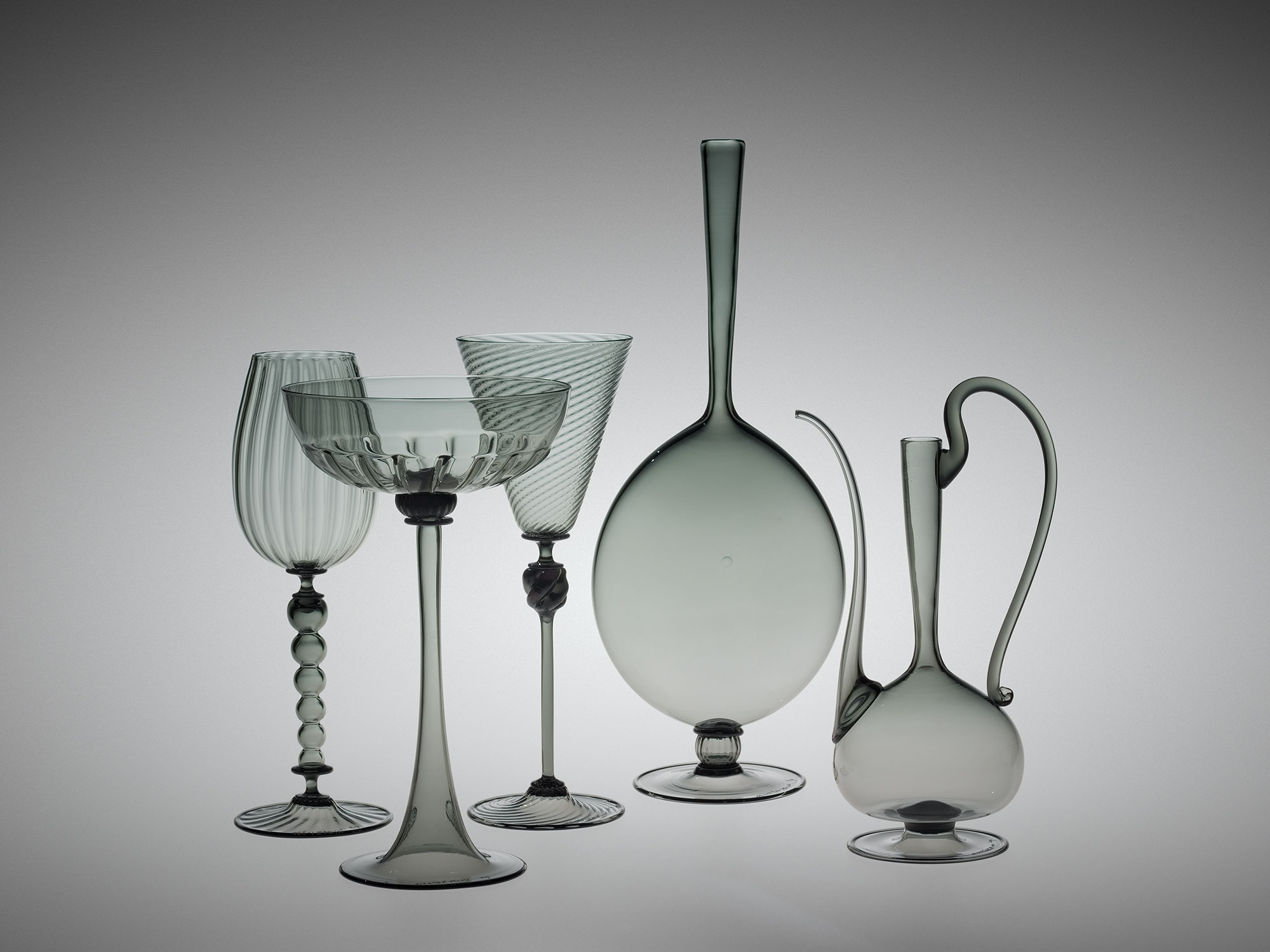 Three clear glass goblets, a clear glass vase, and a clear glass tankard
