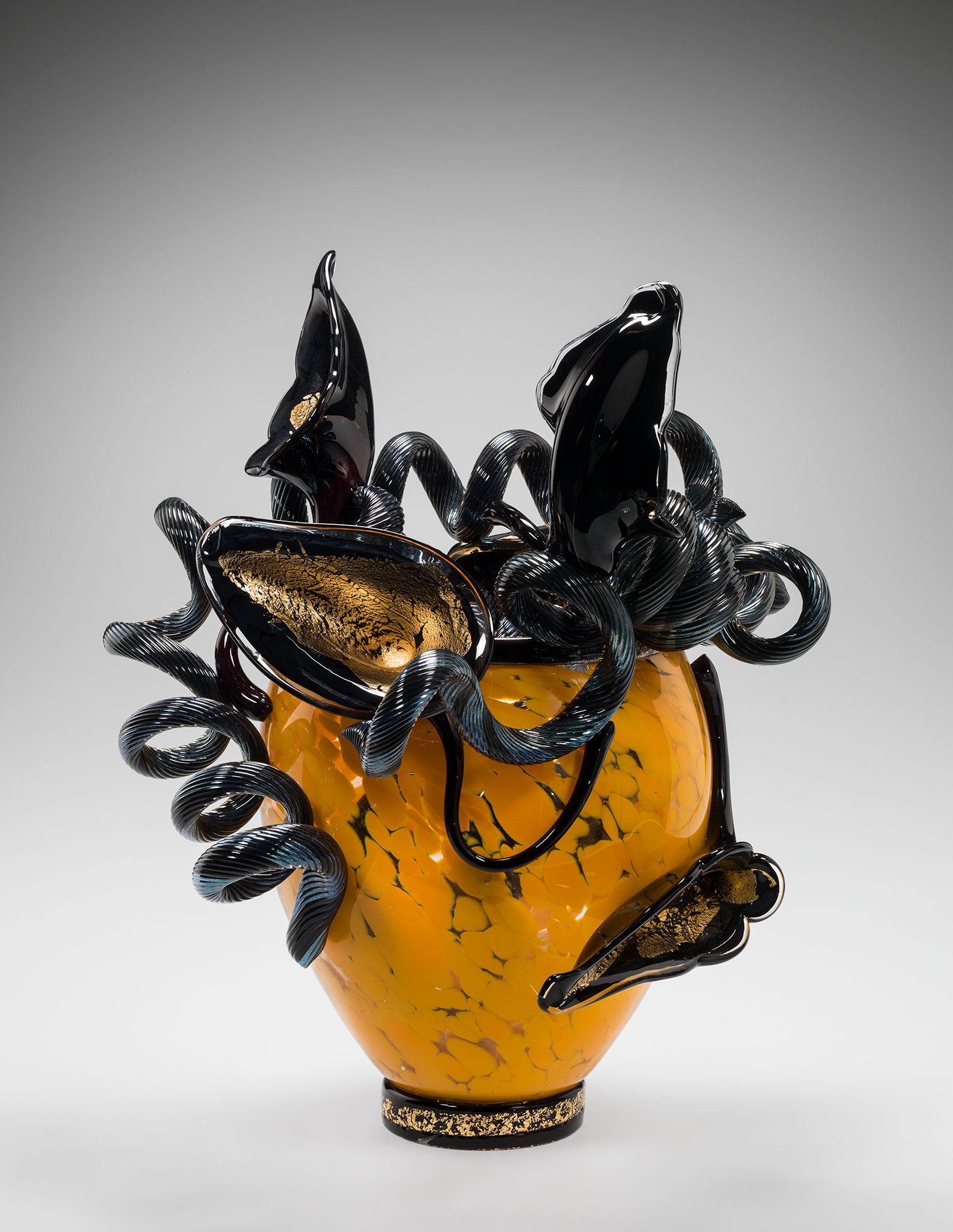 Yellow-orange mottled glass vase with black and gold flower-like structures on top