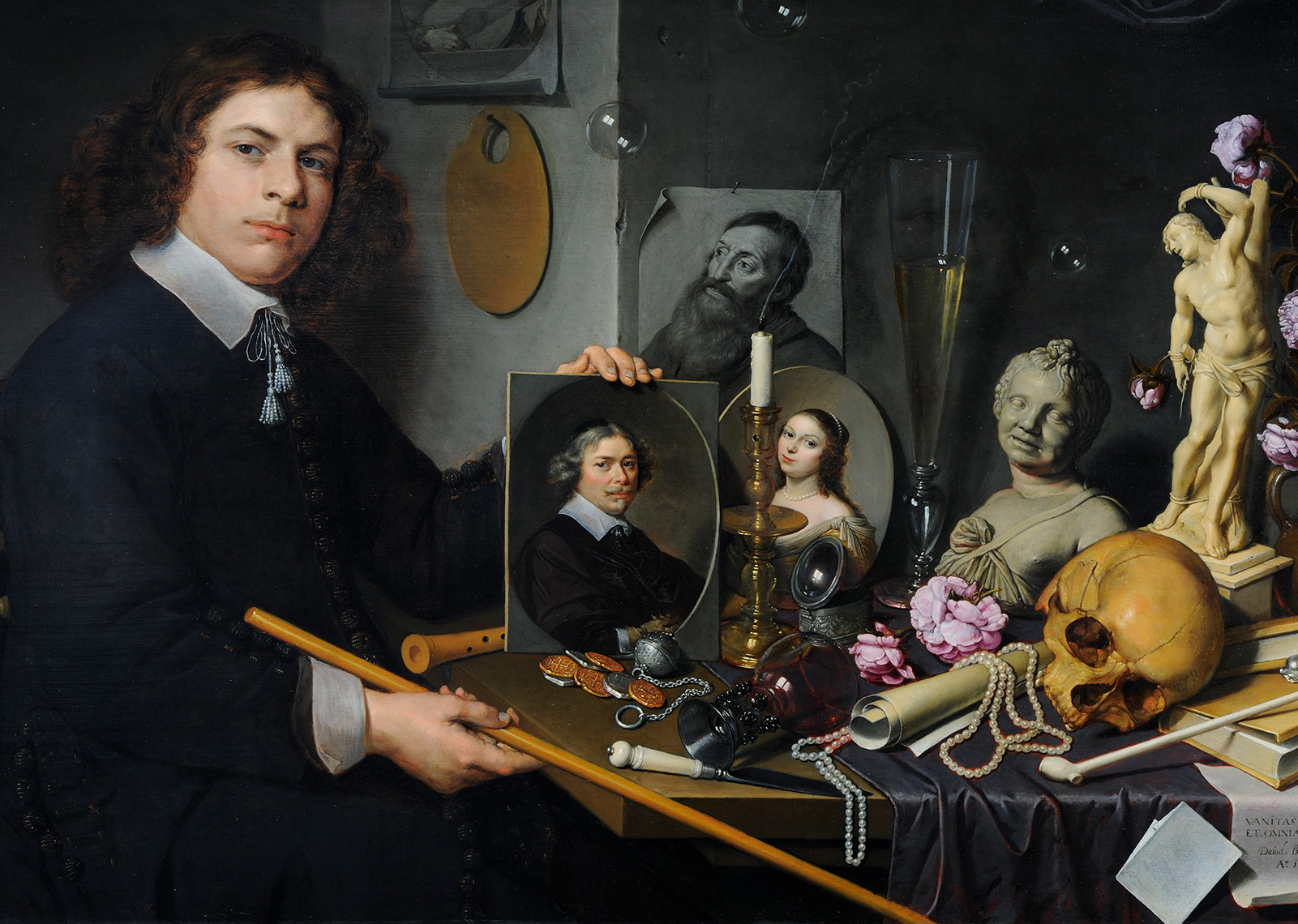Painting of artist seated at table covered with portraits, sculpture, books, and various tools