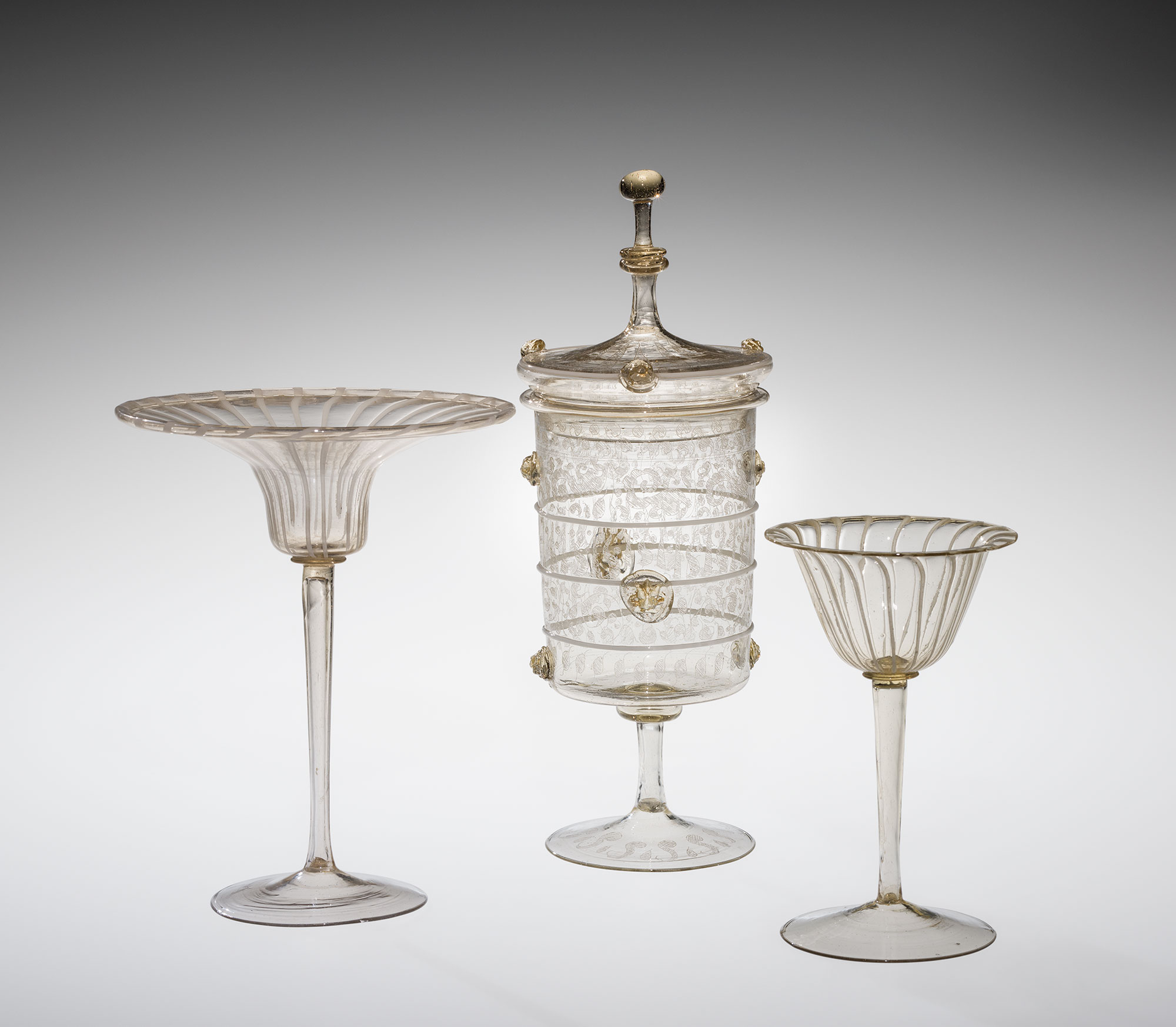 Three clear glass vessels, one with a cover